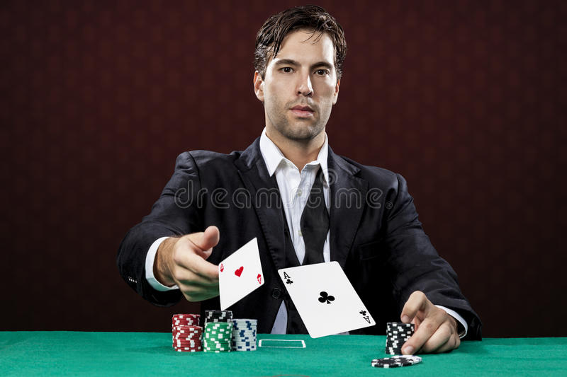 Poker player. On a red background, throwing two ace cards stock photography