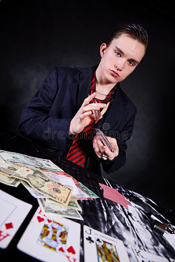 A poker player. Sitting at a table trying to hide his expressions stock images