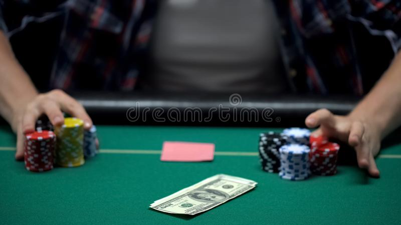 Poker player betting dollars and all his casino chips in cards game, gambling royalty free stock photos