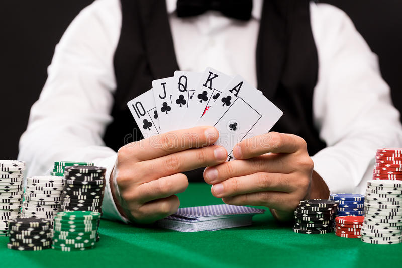Poker player with cards and chips at casino. Casino, gambling, poker, people and entertainment concept - close up of poker player with playing cards and chips at stock photography