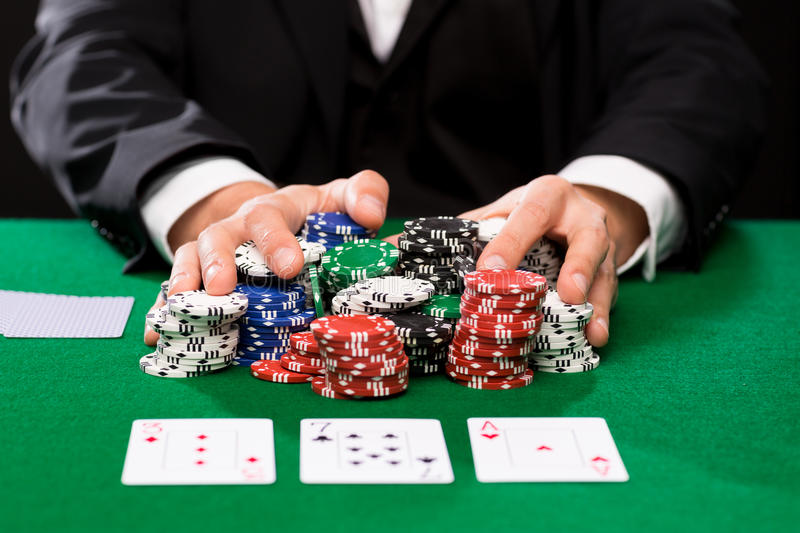 Poker player with cards and chips at casino. Casino, gambling, poker, people and entertainment concept - close up of poker player with playing cards and chips at royalty free stock photo