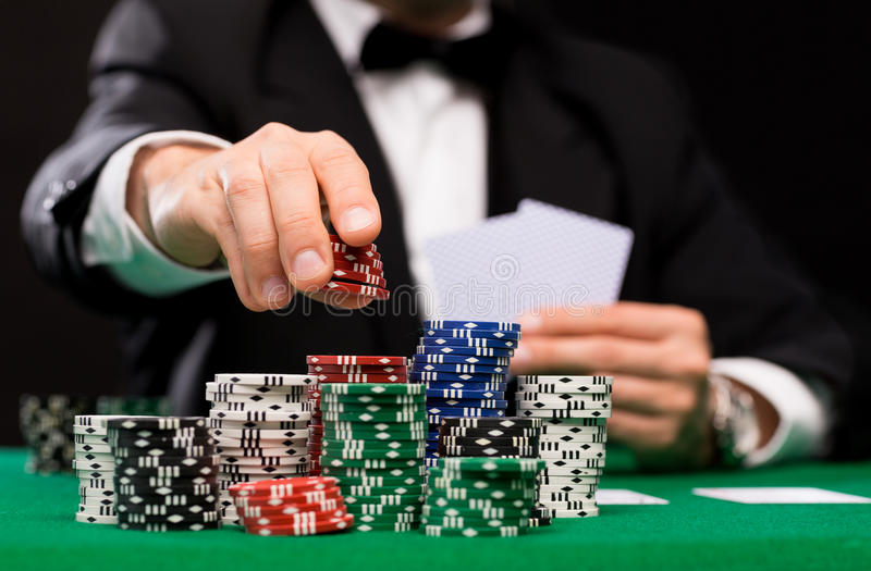 Poker player with cards and chips at casino. Casino, gambling, poker, people and entertainment concept - close up of poker player with playing cards and chips at stock images