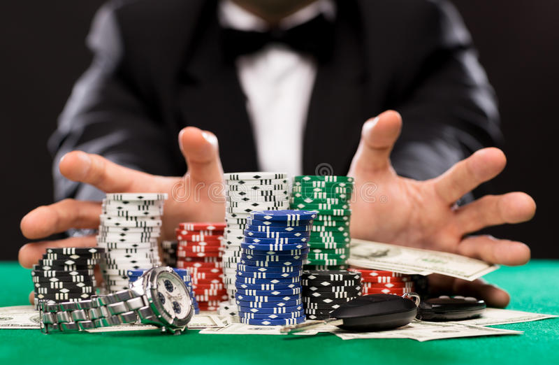 Poker player with chips and money at casino table. Casino, gambling, people and entertainment concept - close up of poker player with chips, money and personal stock photography