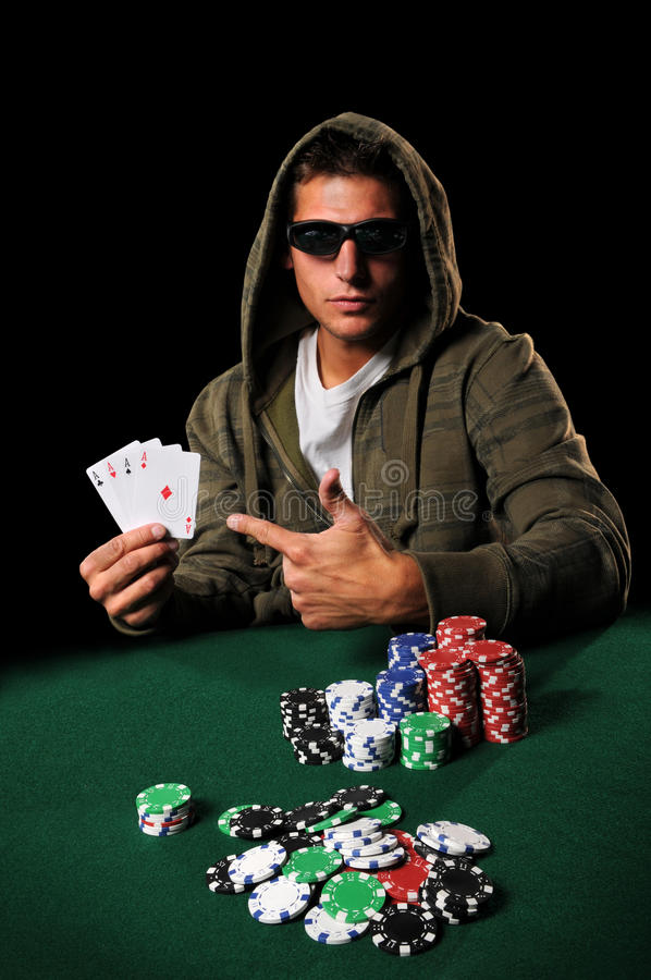 Poker PLayer With Four Aces. Poker player wearing sunglasses pointing to four aces over dark background royalty free stock image