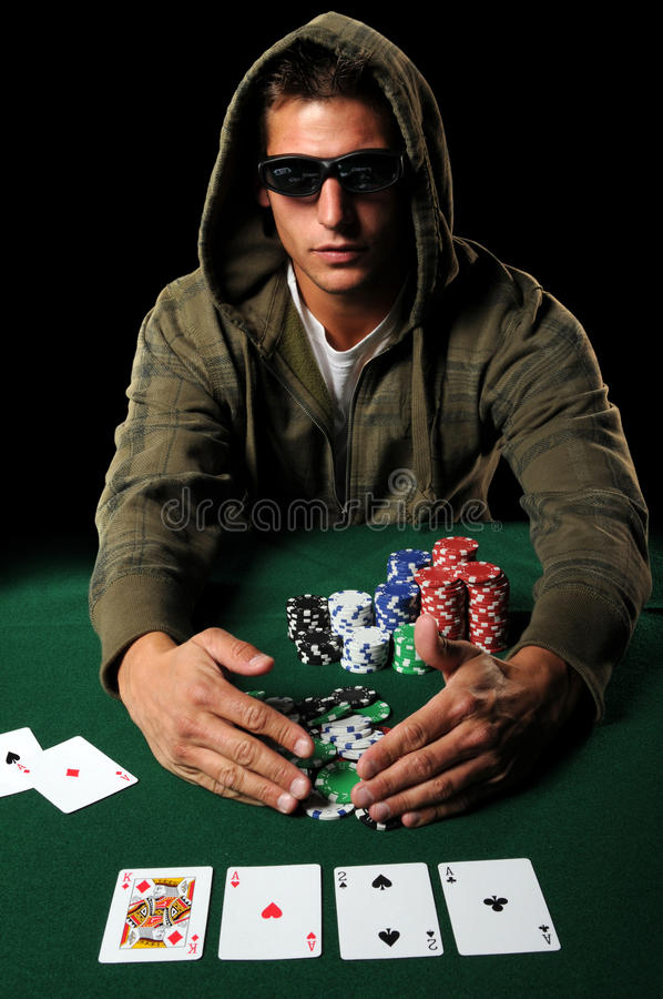 Poker Player Gathering Chips. Poker player with sunglasses gathering winning chips royalty free stock photography