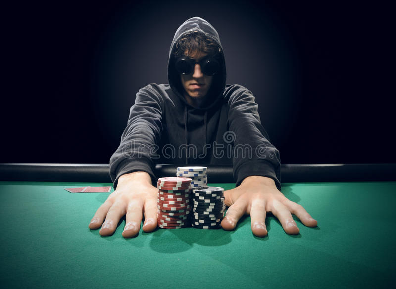 Poker player going all-in. Professional poker player betting everything on one hand royalty free stock image