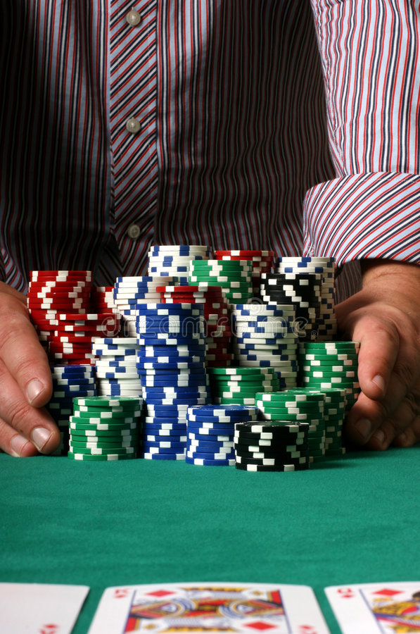 Poker player going all in. Professional poker player betting everything on one hand royalty free stock photo