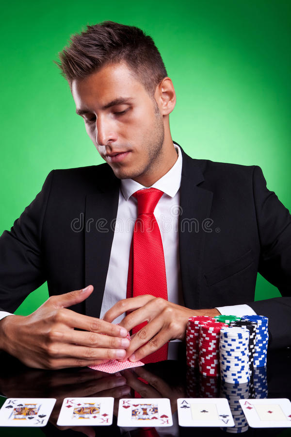 Poker player looking at his cards. On green background royalty free stock photos