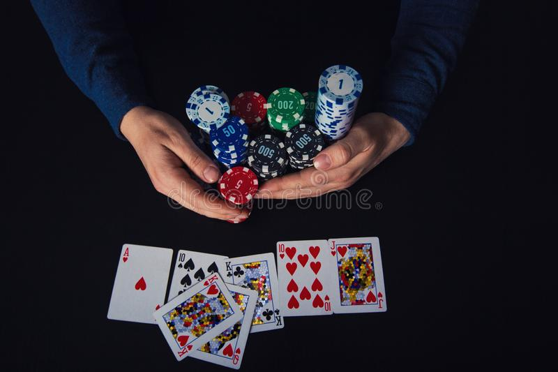 Poker player taking chips to his bank, winning at the casino gaming table having royal flush cards combination. Gambling stock images