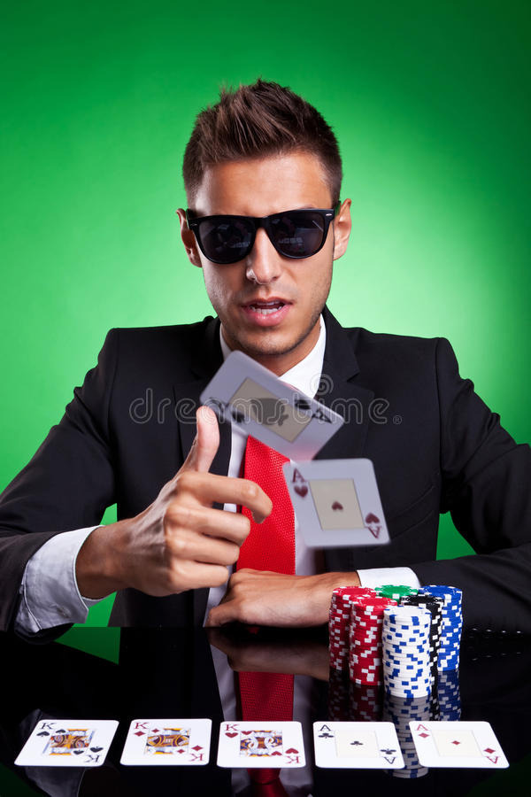 Poker player throwing two ace cards. Poker player, on a green background, throwing two ace cards with full house on table royalty free stock photos