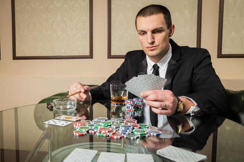 Poker player. Young guy in the casino at the gaming table. Man gambling, card games. Cards, chips, whiskey, cigarettes, poker, card game, gambling - gambling royalty free stock image