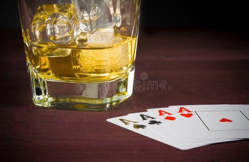 Poker som spelar kort, near wiskeyexponeringsglas royaltyfri bild