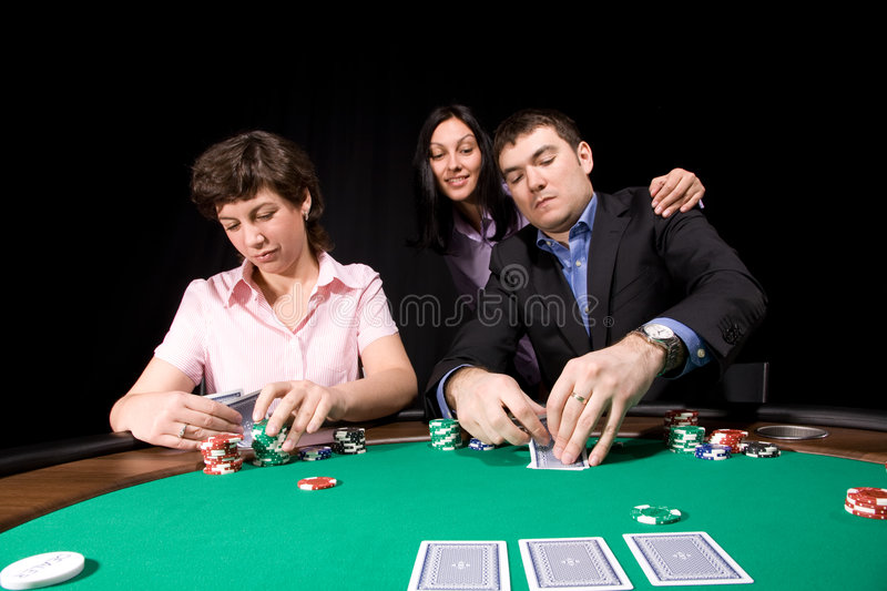 Poker table. Group of young caucasian adults playing poker on green casino felt royalty free stock photography