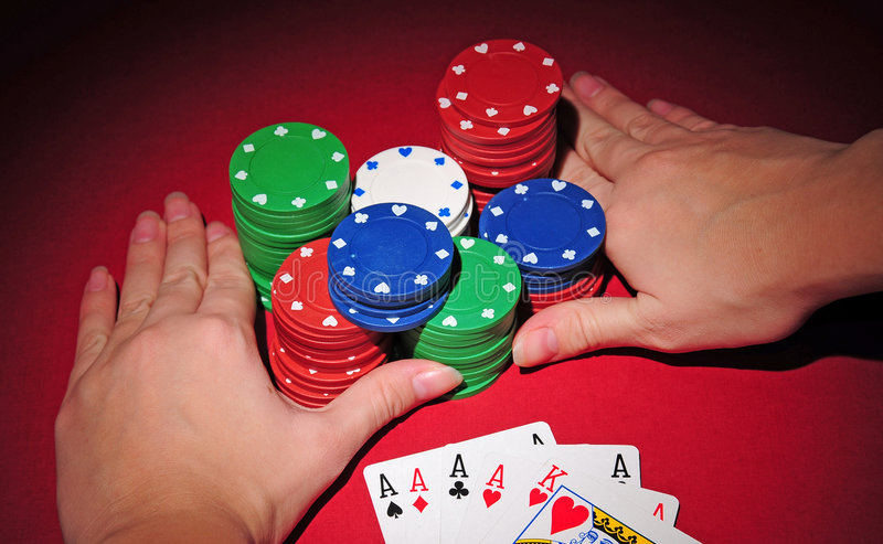 Poker table. All in with four of a kind. Poker player going all in pushing his chips on a red poker table having in his hand four of a kind royalty free stock image