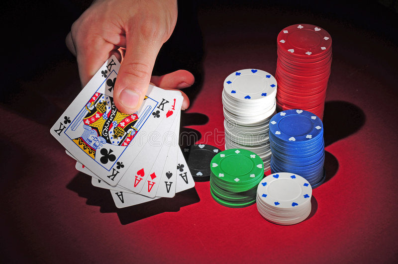 Poker table with full house and chips. Several stacks of poker chips on a red playing table. A man shows his hand with a full house stock photo