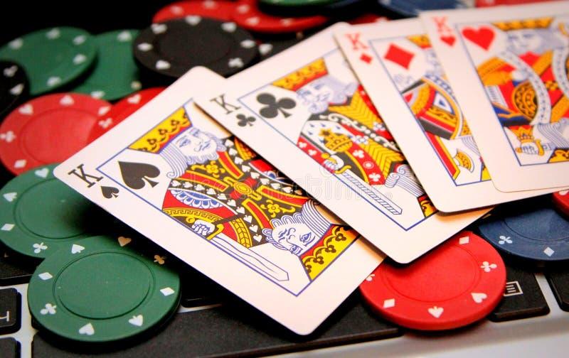 Pokerchiper och fyra konungar på bärbara datorn royaltyfri foto
