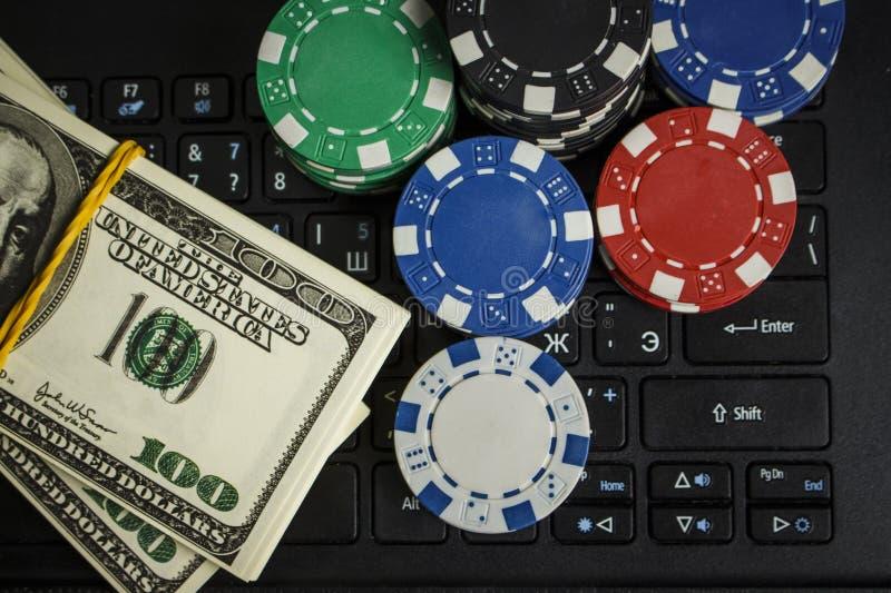 Pokerchiper och packar av dollar på en bärbar dator arkivfoto