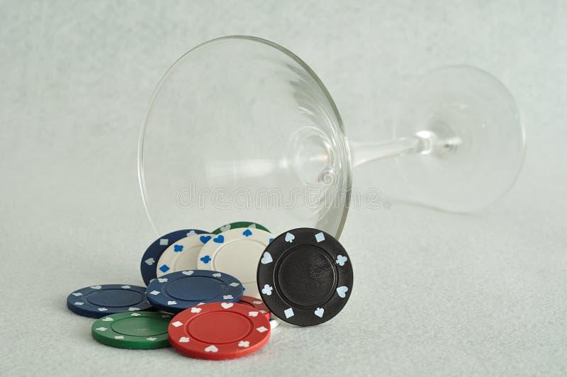 Pokerchiper som faller ut ur ett martini exponeringsglas arkivfoton