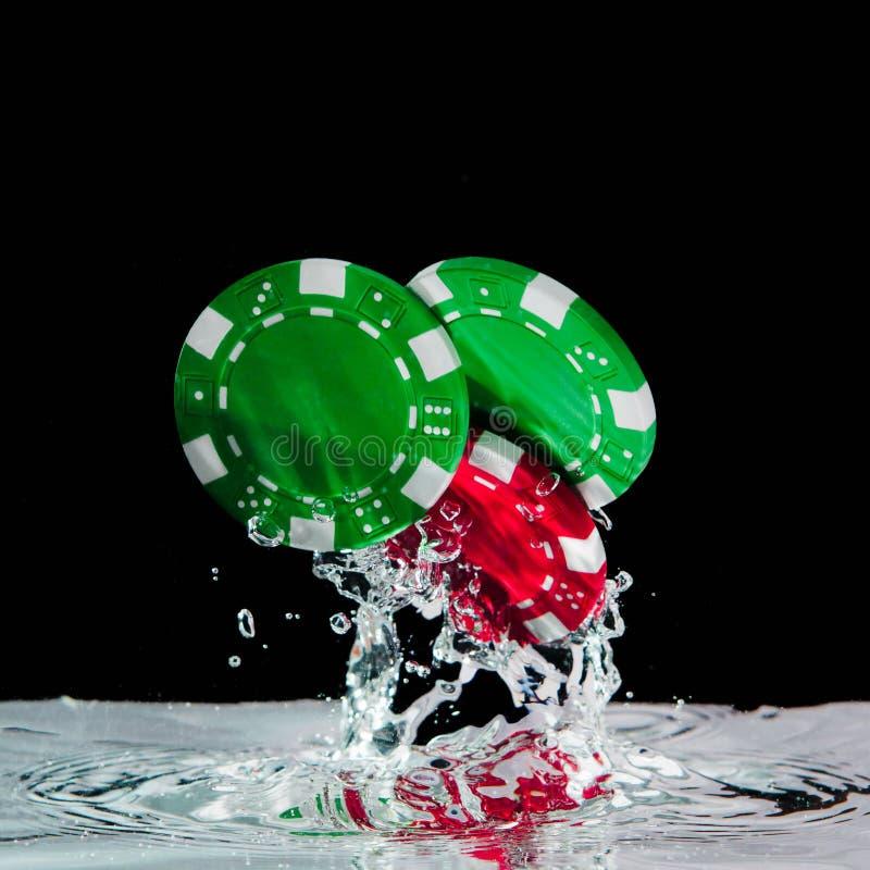 Pokerchips, die in das klare Wasser fallen stockbild