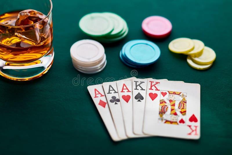 Pokerhand av utsålt, chiper och ett exponeringsglas av whisky arkivfoto