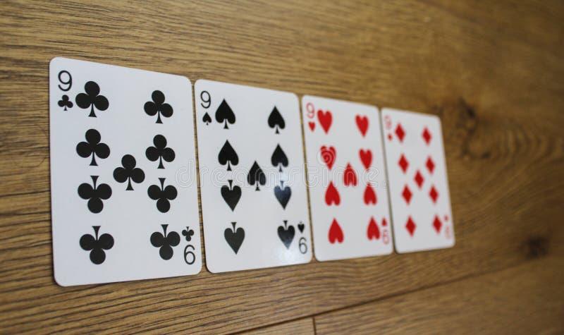 Pokerkort på en träbackround, uppsättning av nines av klubbor, diamanter, spadar och hjärtor royaltyfria bilder