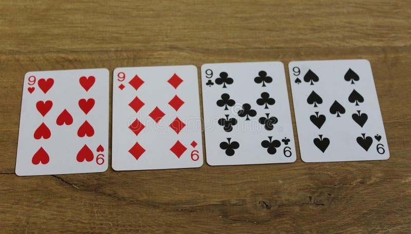 Pokerkort på en träbackround, uppsättning av nines av klubbor, diamanter, spadar och hjärtor royaltyfria foton