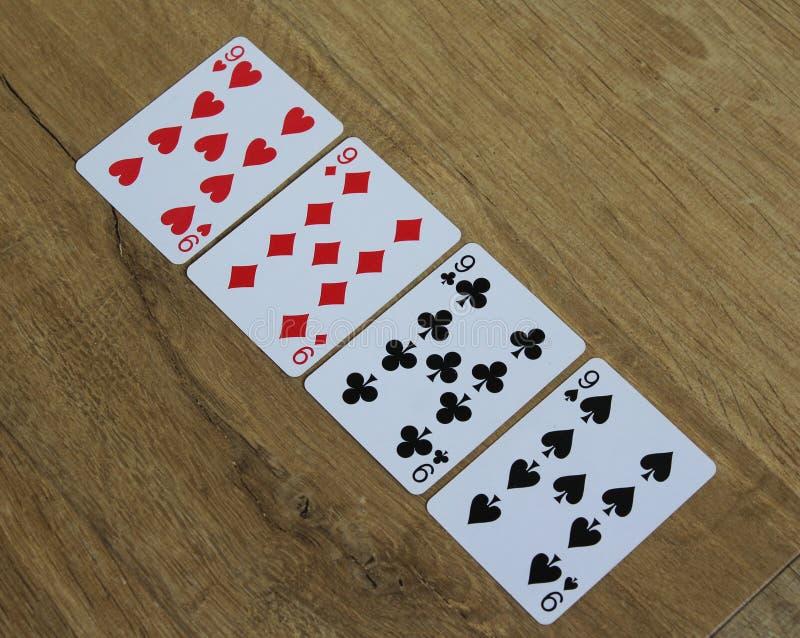 Pokerkort på en träbackround, uppsättning av nines av klubbor, diamanter, spadar och hjärtor fotografering för bildbyråer