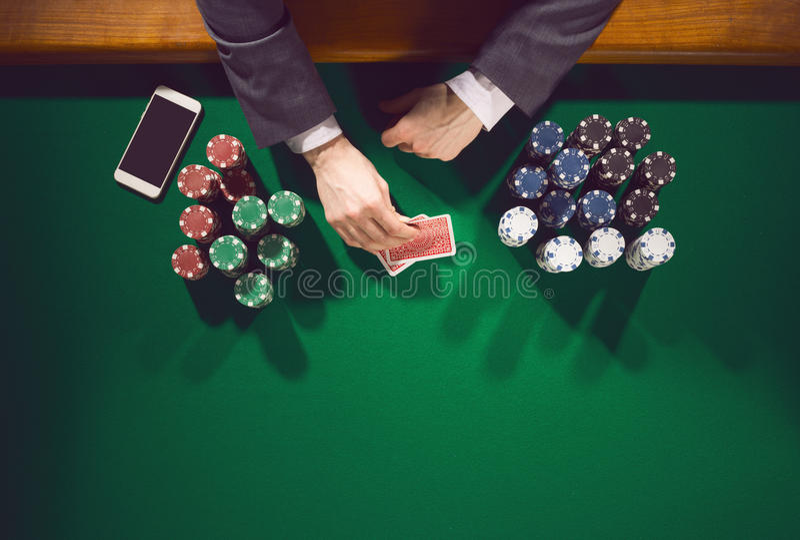 Pokerspelare med smartphonen royaltyfria bilder