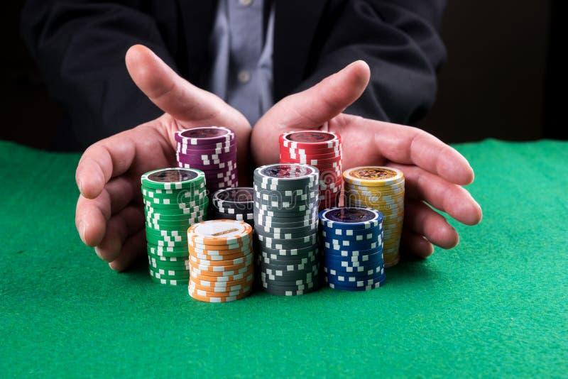 Pokerspelare som går 'allt in 'skjuta hans chiper framåtriktat fotografering för bildbyråer