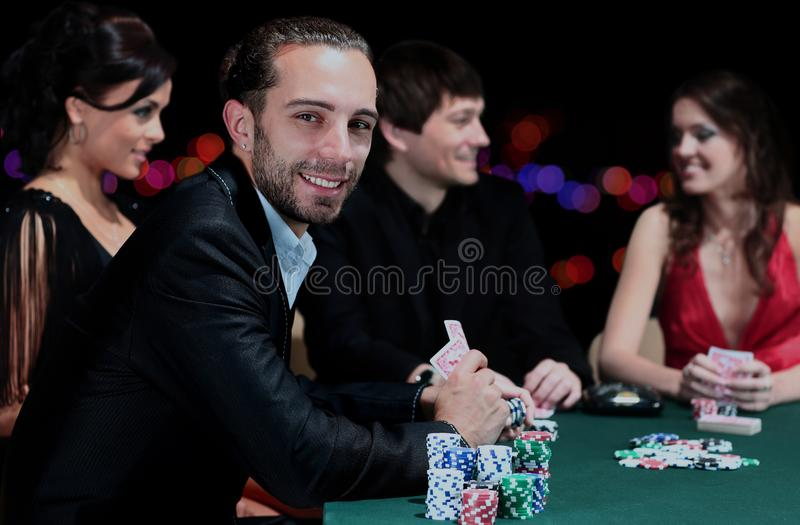 Pokerspelare som sitter runt om en tabell på en kasino royaltyfri bild