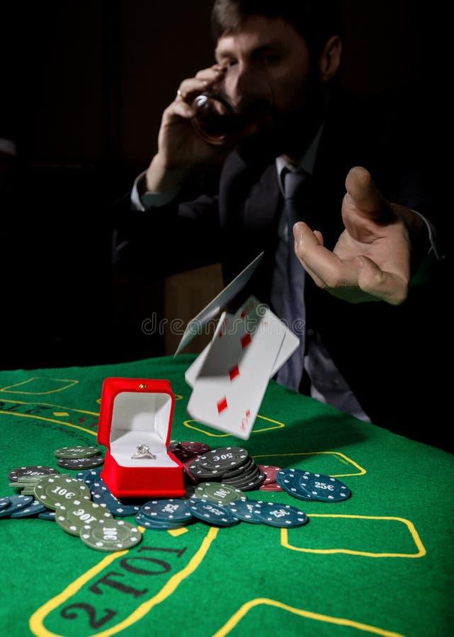 Pokerspelaren som visar en förlorande kombination i kort för en poker, man dricker whisky från sorg royaltyfri foto