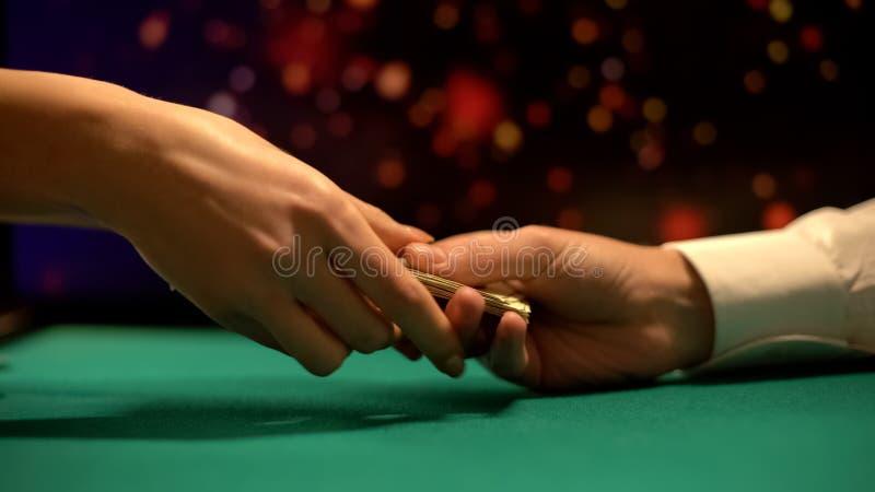 Pokerspieler, der dem weiblichen Croupier, kaufende spielende Chips, Kasino Geld gibt lizenzfreies stockfoto