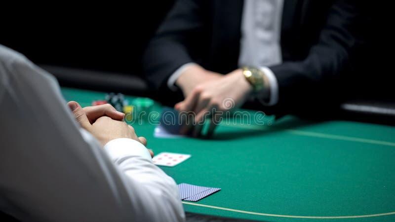 Pokerspieler, der die Kombination von Karten während männliches Croupier wartet, spielend überprüft lizenzfreie stockbilder