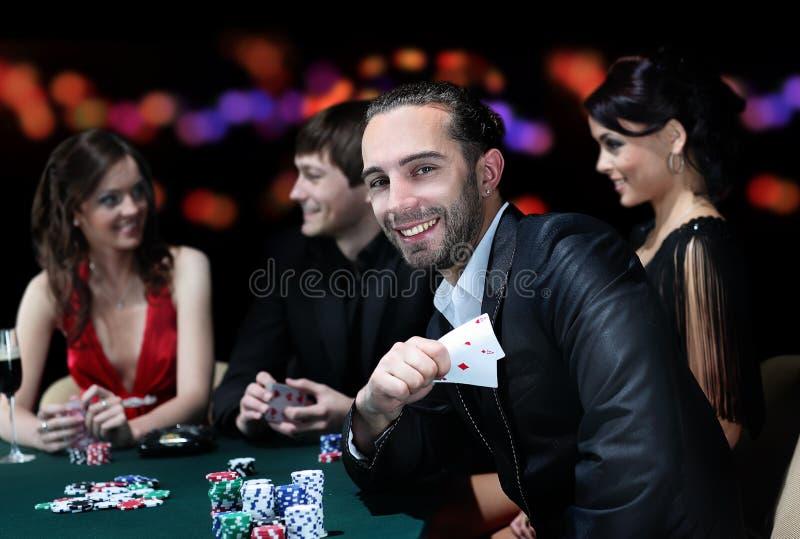 Pokerspieler, die um eine Tabelle an einem Kasino sitzen lizenzfreie stockfotos