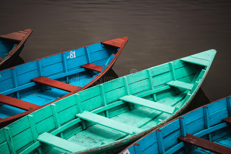 Pokhara canoes. Colourfully painted wooden canoes lined up by the lakeside in Pokhara, Nepal stock photos
