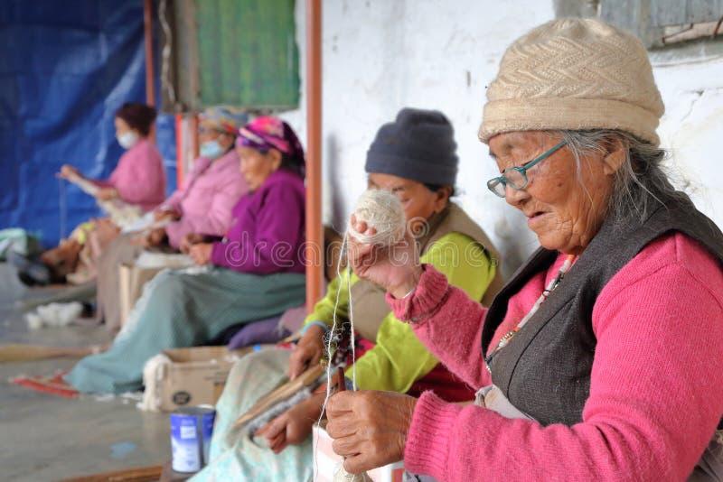 POKHARA, NÉPAL - 8 JANVIER 2015 : Femmes tibétaines tournant la laine au camp de réfugié de Tashi Palkhel Tibetan photo stock