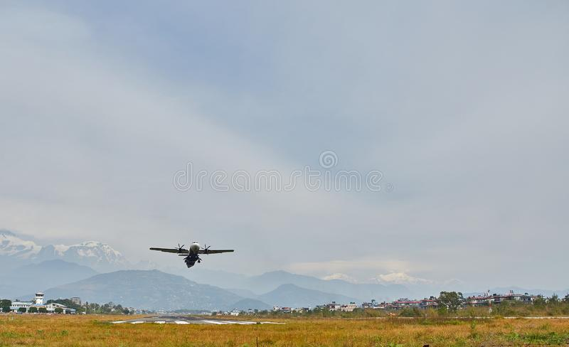 Pokhara, Nepal - April 13, 2019: An airplane of local Nepalese airlines flying against the mountain range of the Annapurna massif stock photos