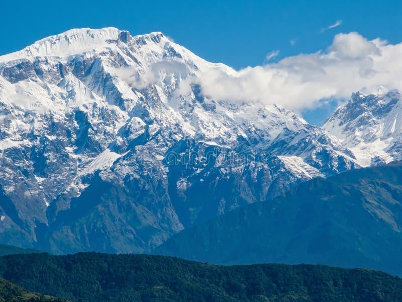 POKHARA, NEPAL: El Himalaya, al norte de Annapurna en el fondo del cielo azul foto de archivo