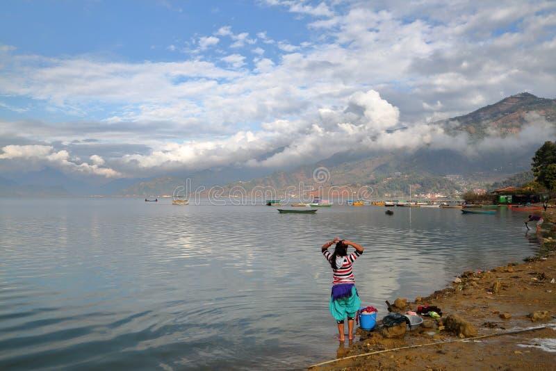 POKHARA, NEPAL: Nepalski kobiety domycie odziewa wzdłuż brzeg Phewa jezioro fotografia stock