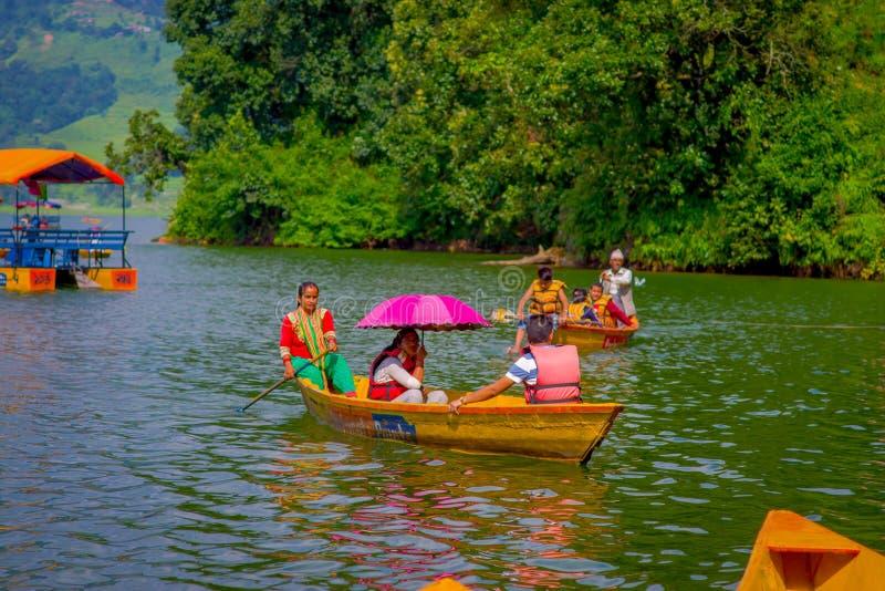 POKHARA, NEPAL - NOVEMBER 04, 2017: Niet geïdentificeerde groep die mensen de boten in het meer binnen paddelen met bij Begnas-me stock fotografie