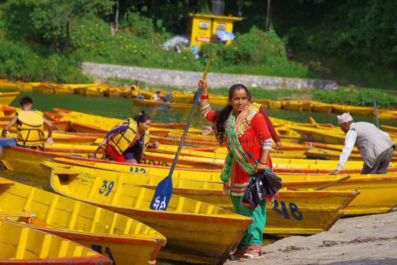 POKHARA NEPAL - NOVEMBER 04, 2017: Oidentifierat kvinnainnehav i hennes hand en skovel med några gula fartyg i Begnasen royaltyfri bild