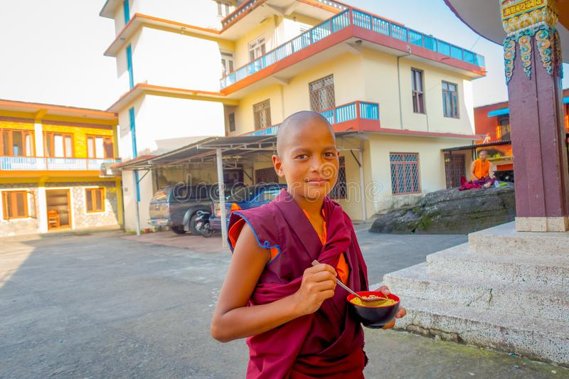 POKHARA, NEPAL - OCTOBER 06 2017: Close up of Buddhist monk teenager holding in his hand a metallic bowl with soup at stock images