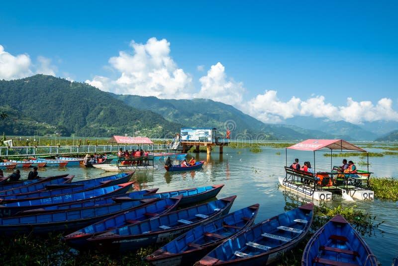 Pokhara, Nepal - October 2019: multi-colored wooden boats and catamarans near the pier on Phewa Feva Lake stock photo