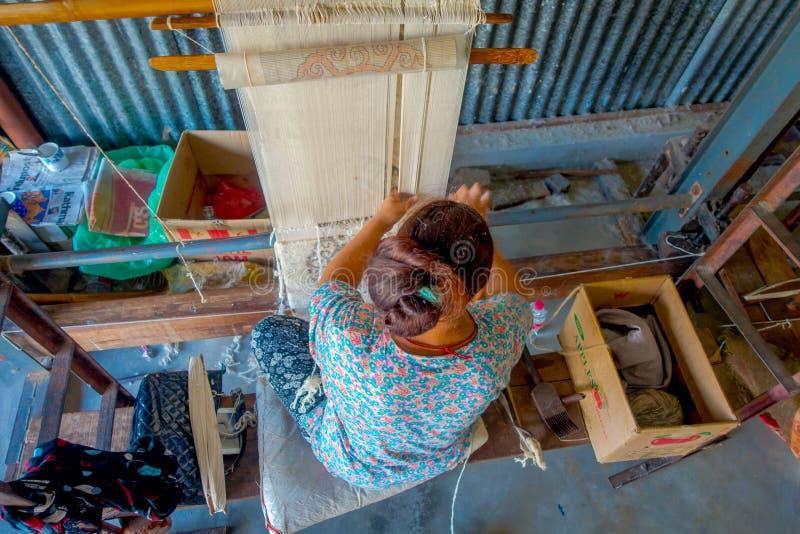 POKHARA, NEPAL - OKTOBER 06 2017: Luchtmening van niet geïdentificeerde vrouw die aan weefgetouw de sjaalkleding van de productie stock foto's