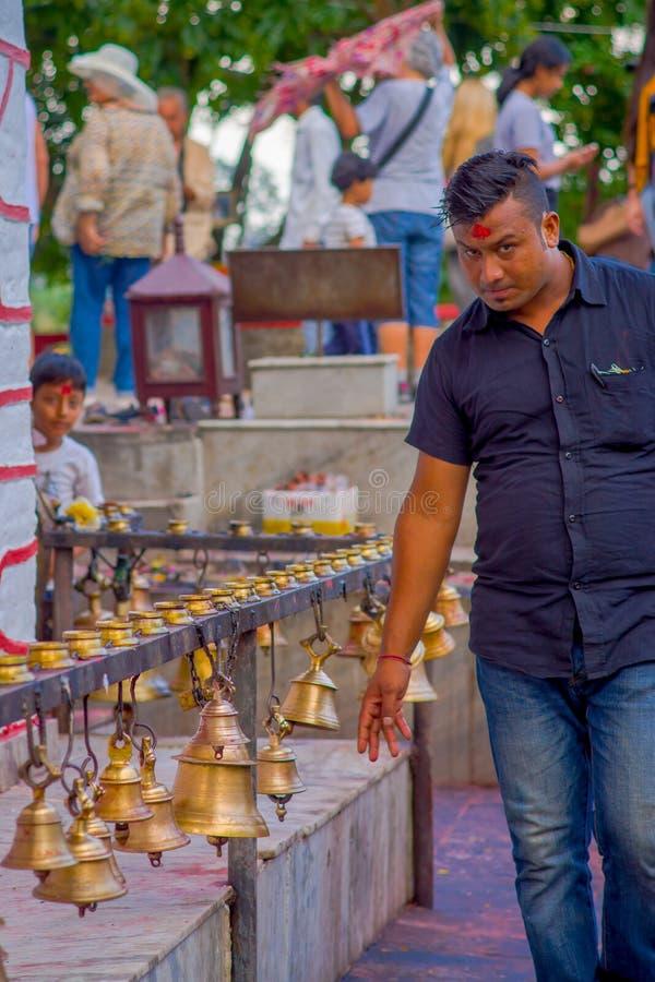 POKHARA, NEPAL 10 OTTOBRE 2017: Uomo d'affari non identificato che porta una maglietta nera e che tocca le campane di differente immagini stock libere da diritti