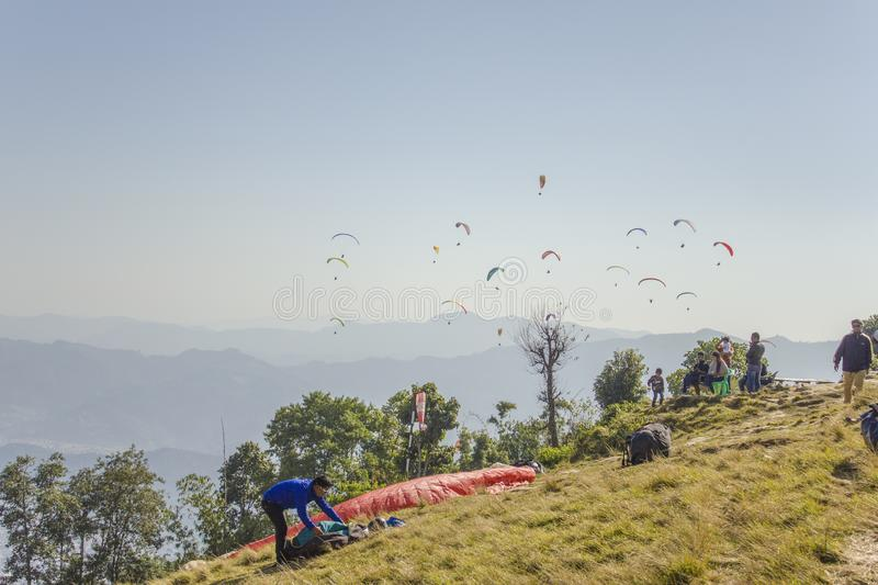 Paraglider prepares to fly on a hillside against the backdrop of a mountain valley and flying stock photos