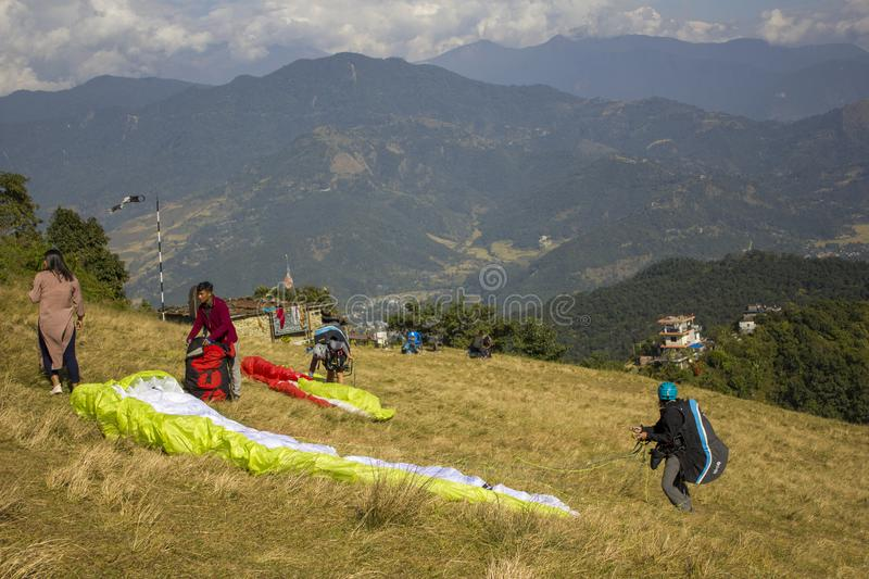 Paragliders on the hillside train to fly against the backdrop of a green mountain valley and clouds royalty free stock images