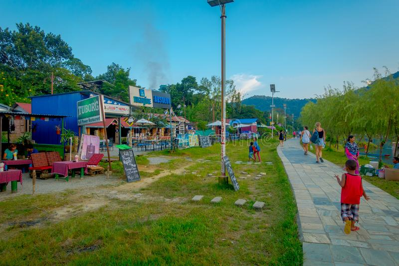 Pokhara, Nepal - September 04, 2017: Unidentified people wlaking in the stoned lakeshore with some food trucks seling. Food, in a beautiful day in Pokhara city royalty free stock images
