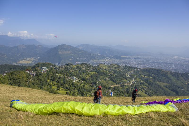 two paragliders prepare parachutes for takeoff on the hillside against the backdrop of the city in a royalty free stock images