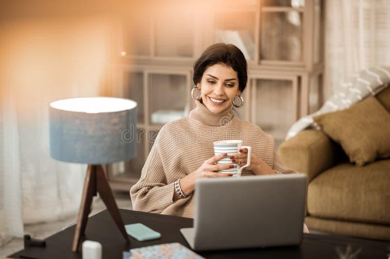 Pokojowa atrakcyjna dama wydaje czas w domu i ogląda wideo obrazy stock